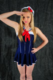 Sailor Girl. Young female fashion model wearing a sailor outfit saluting to the camera standing against a charcoal back drop stock photo
