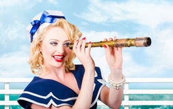 Sailor girl pin-up looking through telescope Stock Images