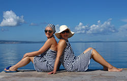 Sailor girls. Girls dressed in sailor clothes sitting near the Adriatic sea with their backs leaning against each other Stock Image