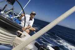 Sailor At Helm of Sailboat. Sailor at the helm of a yacht in the ocean against blue sky stock images