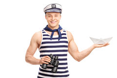 Sailor holding binoculars and a paper boat. Cheerful young sailor holding binoculars and a paper boat isolated on white background Royalty Free Stock Photography