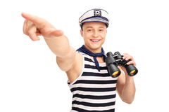 Sailor holding binoculars and pointing with his hand. Male sailor holding binoculars and pointing with his hand isolated on white background Royalty Free Stock Photos