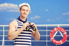 Sailor holding binoculars and standing on a boat Royalty Free Stock Images