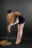 Sailor with long fair hair. Girl bends down and pulls rope in stage costume of sailor, long hair fallen loose Stock Images