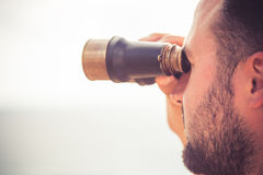 Sailor man looking through the binoculars. Against blue sky background Stock Photos