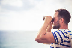 Sailor man looking through the binoculars. Against blue sky background Stock Image