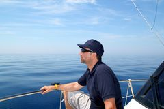 Sailor man sailing boat blue calm ocean water Royalty Free Stock Images