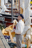 Sailor man in vintage clothes. GRISSLEHAMN - JUN 13, 2015: Male sailor in vintage clothes and blue hat standing in old sailing ship in the public event Stock Images