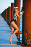 Sailor model  in stylish swimsuit and captain hat posing sexy on the wooden pier Stock Image