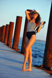 Sailor model in stylish swimsuit  holding binoculars and standing on the wooden pier Royalty Free Stock Photos