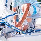 Sailor on a modern yacht. Body of a sailor working on a modern white yacht Royalty Free Stock Photos