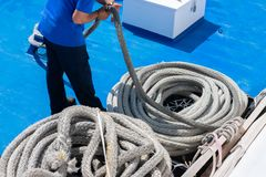Free Sailor On The Ship Is Giving Mooring In The Port. The Rope Is Coiling And Wounding In A Spiral Stock Photos - 161474853