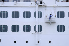 Sailor paints the ship. Current face lifting of the ship. The ship is moored at quay of Neva Royalty Free Stock Image