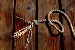 Sailor rope and knot on a wooden pier at the seaside royalty free stock photography