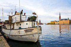 Sailor's old white boat on city background. Sailor's old white boat on old city background under cloudy sky Royalty Free Stock Images