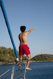 Sailor showing the island. In the front of a sail boat royalty free stock photos