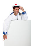 Sailor smiling. Whilst stood by a blank poster stock image