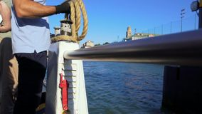 Sailor standing on deck and holding rope, water transportation in Venice. Stock footage stock video
