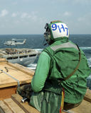 Sailor watching Helicopter. A sailor sits and watches a helicopter operate on a nearby ship Stock Images