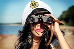 Sailor woman with binoculars is taking a walk on the seacoast Stock Photo