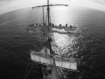 Sailors aloft furling a sail at sea Stock Images