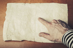 Sailors hand pointing some place on empty paper. Sailors hand pointing some place on the empty old crumpled paper sheet, pirate map copy-space template. Vintage stock images