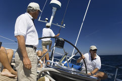 Sailors At Helm Of Sailboat Stock Photo