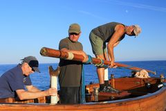 Sailors holding wooden spar. People taking wooden spar off the sailing boat stock photography
