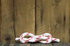 Sailors knot on a wooden background for concepts. Royalty Free Stock Photos