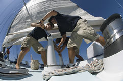 Sailors Operating Windlass On Yacht. Low angle view of sailors operating windlass on yacht Royalty Free Stock Images