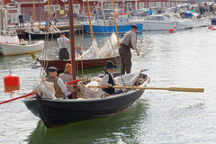 Sailors in vintage clothes using the oars old sailing ship. GRISSLEHAMN - JUN 13, 2015: Sailors in vintage clothes using the oars in old sailing ships in the Royalty Free Stock Images