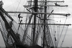 Sailors working aloft in the rigging of a traditional tallship Royalty Free Stock Images