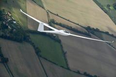 Sailplane die over landbouwgrond stijgt. stock afbeelding