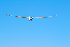 Sailplane. A sailplane in front of a blue sky glides through the air without its own motor drive Stock Photo