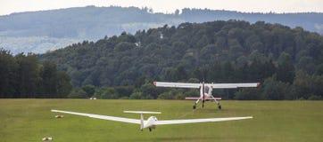 Sailplane och en bogseraflygplanstart på ett flygfält fotografering för bildbyråer
