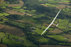 Sailplane soaring across the countryside. Stock Images