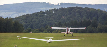 Sailplane and a towing aircraft starting on an airfield. A sailplane and a towing aircraft starting on an airfield stock image