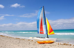 Sails and beach. Sea beach sunshine colourful sails boat red blue beach resort vacation tropical royalty free stock image