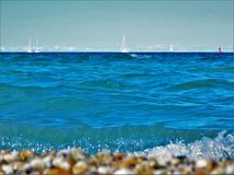 Sails on the Horizon Pebbles on the Land Royalty Free Stock Images