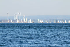 Sails and Propellers. The view of the sailboats and wind generators on the blue sky and water background Royalty Free Stock Image