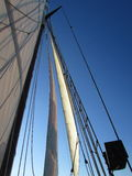 Sails and Ropes. My view of the sails  and blue sky on a recent Schooner ride as we sailed up the river towards the sunset Royalty Free Stock Photos