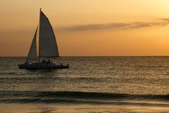 Sails in Sunset. Catamaran with sails in silhouette on calm waters against orange colored sunset stock image
