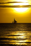 Sails in the Sunset. A sailboat silhouetted against the setting sun Royalty Free Stock Photography