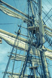 Sails and tackles of a sailing vessel on a background of the sky Stock Images