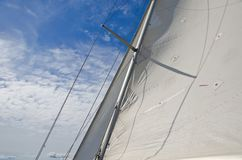 Sails of a yacht against a blue sky Royalty Free Stock Photo