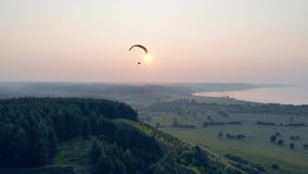 Sailwing is drifting high in the sunlit sky. Paraglider in the sky.