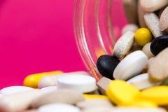 Saindo das drogas das vitaminas dispersadas e derramadas para fora perto de um recipiente de vidro branco aberto do frasco Tratam imagens de stock royalty free
