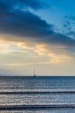 Sainlboat на штиле на море в свете сини желтого цвета восхода солнца Стоковые Изображения
