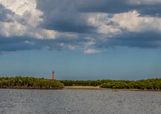 Saint Augustine lighthouse under some broken clouds with blue grey sky in the background. Mangroves in the foreground make the red lighthouse stand out Stock Photos