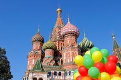 Saint Basil`s Cathedral in Moscow on Red Square. Saint St Basil`s Cathedral in Moscow on Red Square against a blue sky and with a bunch of colorful balloons in Stock Images
